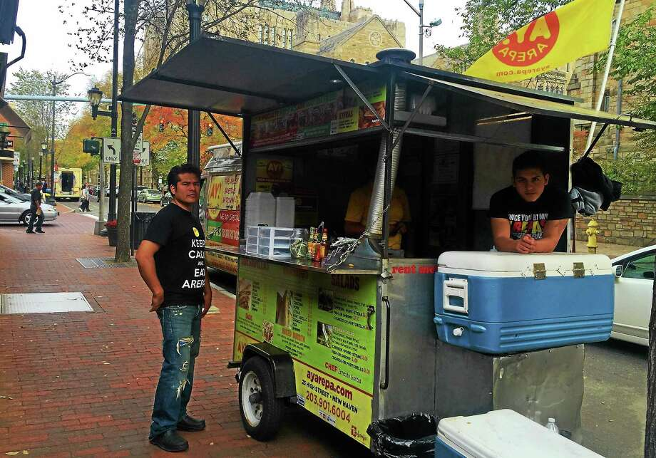 Ernesto Garcia, left, stands next to his food stand, Ay! Arepa, on York Street in New Haven on Thursday. Garcia was asked to shut down last week by city officials due to zoning restrictions and reopened in a new spot Thursday. Photo: Esteban L. Hernandez — New Haven Register