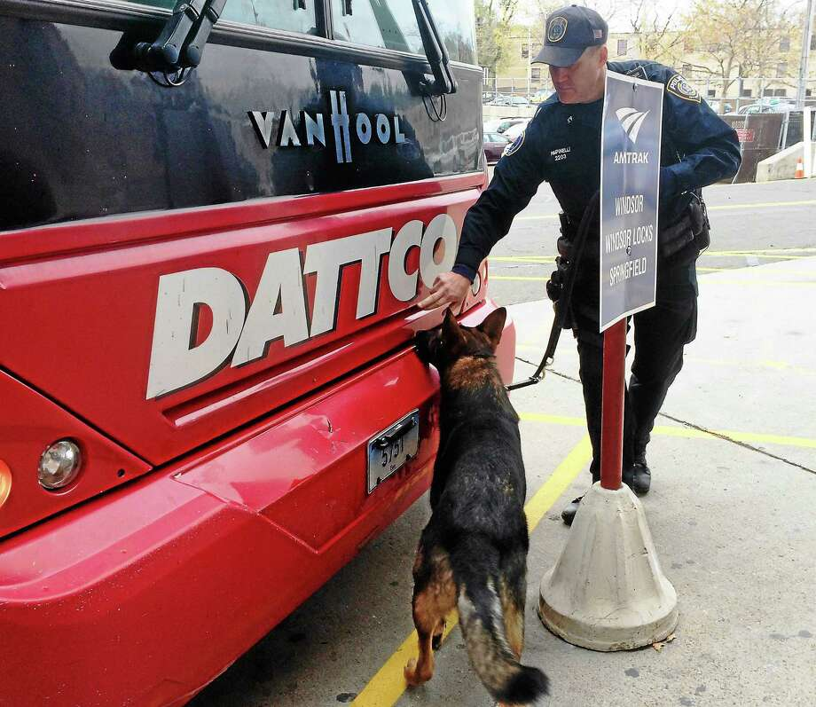 MTA Police Officer Kevin Pimpinelli and his canine partner Johnny check a departing bus Wednesday morning at Union Station in New Haven. Photo: Wes Duplantier — New Haven Register