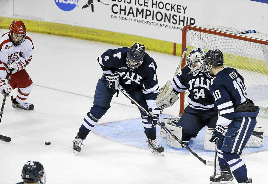 Boston University's Danny O'Regan, far left, gets ready to shoot the game-winning goal past Yale goaltender Alex Lyon (34), Rob O'Gara (4) and Mitch Witek (10) during overtime of an NCAA regional semifinal game in March in Manchester, N.H. Photo: Elise Amendola — The Associated Press File Photo   / AP