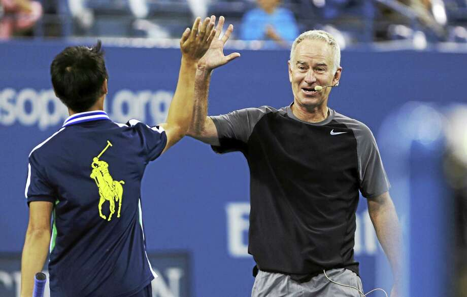 John McEnroe high-fives a ball boy during an exhibition match last year at the U.S. Open in New York. Photo: Charles Krupa — The Associated Press File Photo   / AP