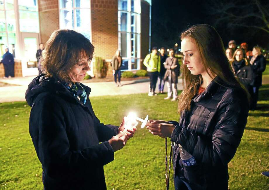 Isabel Evelein, left, honorary consul of France in Hartford, shares the light from her candle with Quinnipiac University freshman Marissa Davis, 18, during a vigil in remembrance of the victims of last week's terror attacks in Paris, Wednesday in Hamden. Photo: Arnold Gold — New Haven Register
