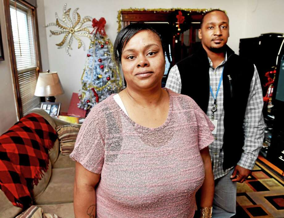Kireeshia Suggs, center, in her home in New Haven with New Haven Trauma Coalition Care Coordinator Bryan Marks. Photo: Arnold Gold — New Haven Register