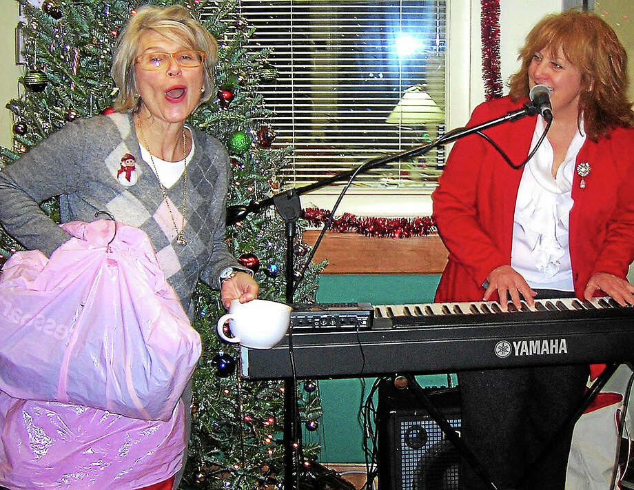 Fa, la, la — Retiring Pat Kral, left,  sings along during a Christmas dinner at the Community Dining Room where she was executive director for 25 years. Photo: Contributed Photo