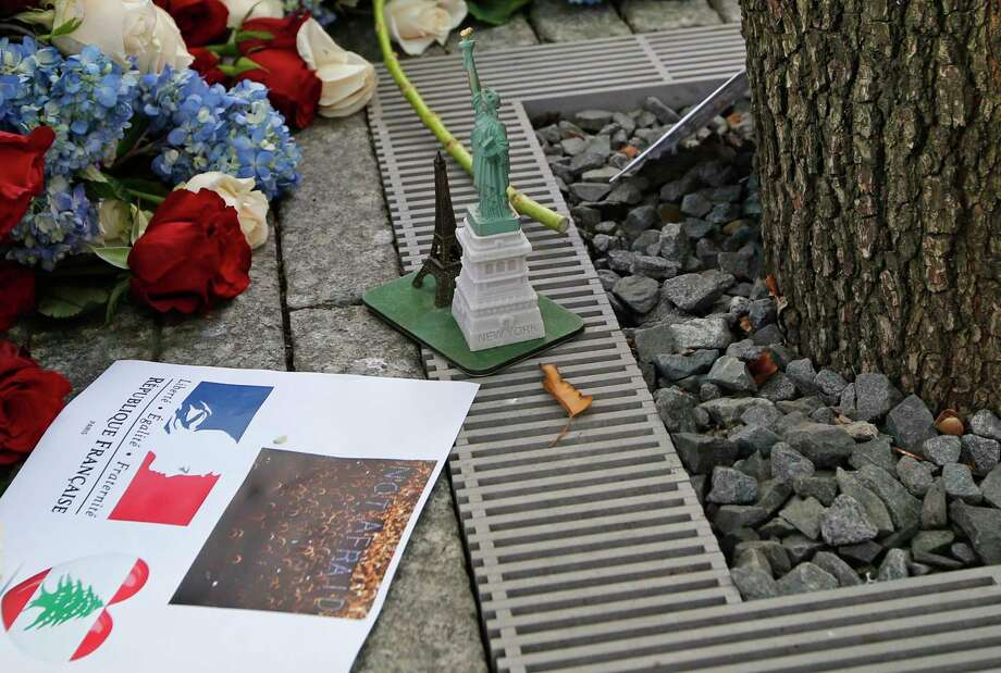 Items left at the foot of the Survivor Tree, part of the 9/11 Memorial, following a tribute to victims of the Paris terrorist attacks, include a replica of the Eiffel Tower and another of the Statue of Liberty, along with red, white and blue flowers in New York. Photo: AP Photo   / AP