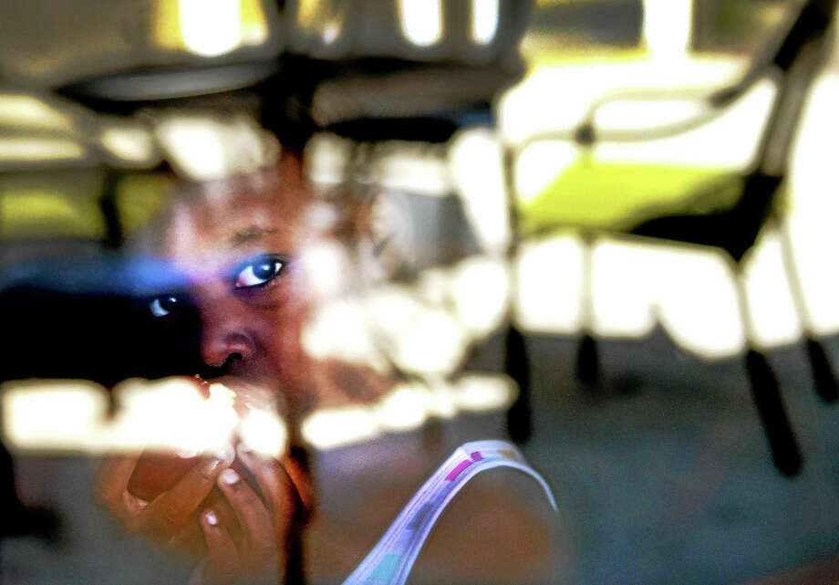 (Peter Hvizdak - New Haven Register)  Serenity Earl, 5, surrounded by reflections of an outdoor patio,  eats an apple in the lobby dining area of the Premier Hotel and Village Suites on Long Wharf Drive in New Haven Sunday. Serenity, her mother, and brother where moved to the hotel by their landlord because of deplorable conditions at their Church Street South apartment. Photo: ©2015 Peter Hvizdak / ©2015 Peter Hvizdak