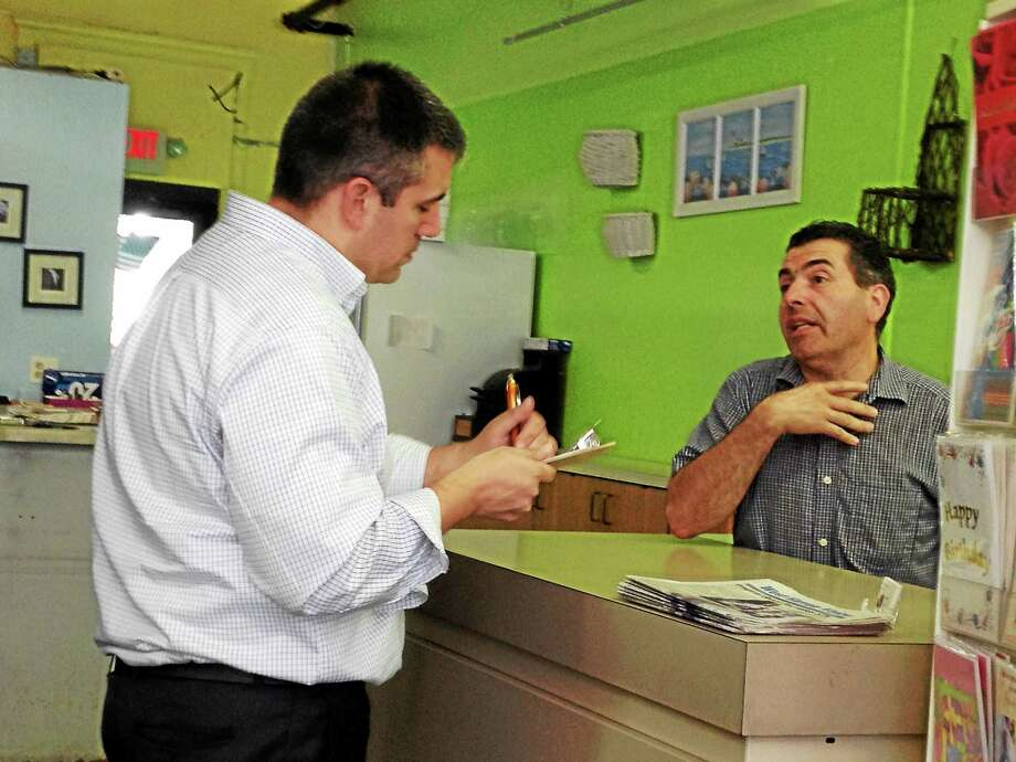 MARK ZARETSKY — NEW HAVEN REGISTER  Pascale speaks with The Flower Affair employee Pete Macchiarelli. Photo: Journal Register Co.
