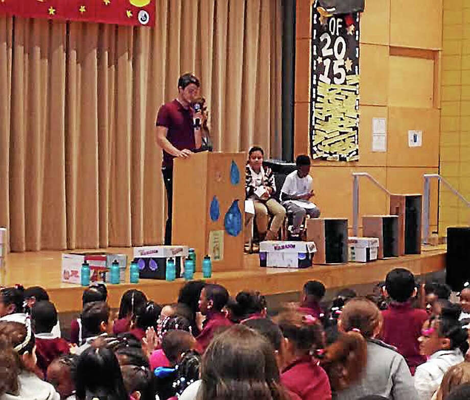 King/Robinson Magnet School physical education and wellness facilitator Steve Siena addresses students during an assembly after the Regional Water Authority donated 600 reusable water bottles to the school. (Brian Zahn - New Haven Register) Photo: Journal Register Co.