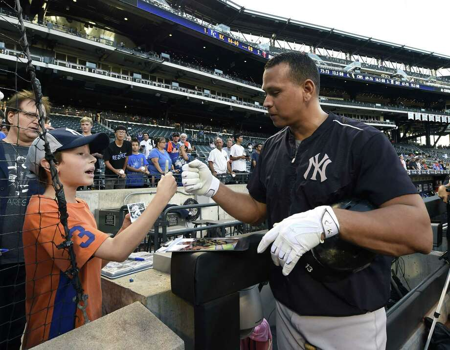 New York Yankees DH Alex Rodriguez bumps fists with Alex Weissman, 11, of Livingston, N.J., after signing an autograph during batting practice before Friday's game against the New York Mets at Citi Field in Queens. Photo: Kathy Kmonicek — The Associated Press   / FR170189 AP