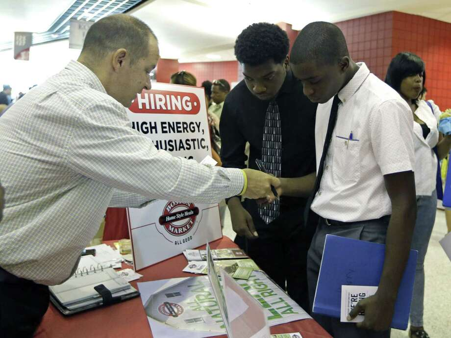 Mario Polo, of Boston Market, left, talks to job seekers Herby Joseph, right, and Kingsly Jose, center, at a job fair June 10 in Sunrise, Fla. Photo: Associated Press   / AP