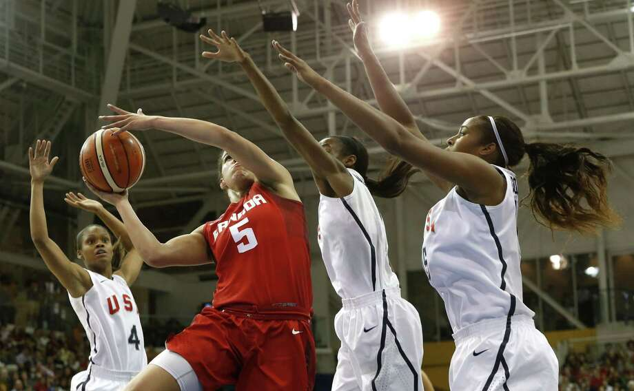 Canada's Kia Nurse, second from left, goes up for a shot against United States' Moriah Jefferson, from left, Shatori Walker and Alaina Coates during the first quarter of the women's basketball gold medal game at the Pan Am Games, Monday in Toronto. Photo: Julio Cortez — The Associated Press    / AP