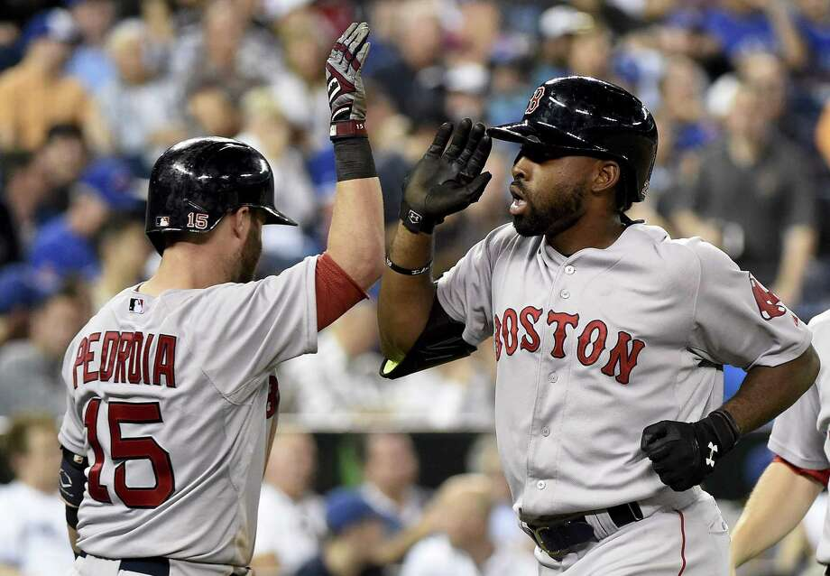 Jackie Bradley, right, celebrates his two-run home run with teammate Dustin Pedroia during the ninth inning on Saturday. Photo: The Associated Press   / CP