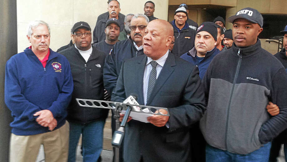 Connecticut NAACP President Scot X. Esdaile, center, speaks in support of Firefighter Aaron Brantley, right, Tuesday in New Haven. Photo: Ryan Flynn — New Haven Register