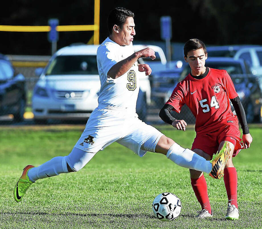 David Pereira (center) of Amity and Mitch Manware of Cheshire fight for the ball in the first half of Chehsire's 5-1 win on 10/19/2015. Photo: Arnold Gold -- New Haven Register