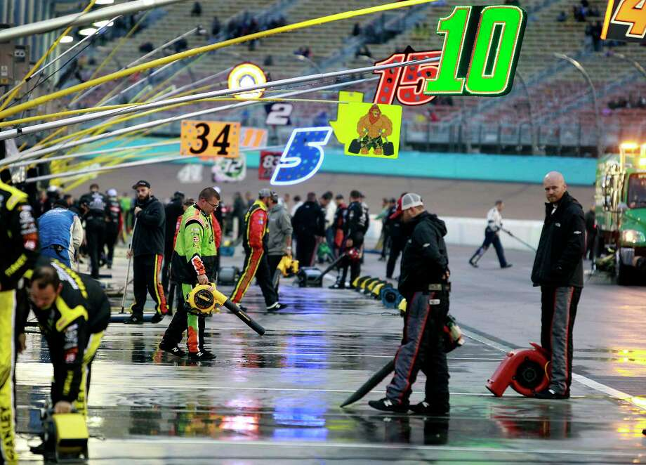 Pit crews work to dry their pit stalls during the NASCAR race at Phoenix International Raceway on Sunday. Photo: Ralph Freso — The Associated Press   / FR170363 AP