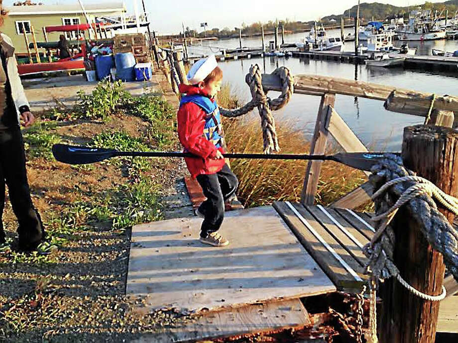 Sawyer Christmann, 7, brings his paddle to the dock at Quinnipiac River Marina Tuesday morning. Photo: Brian Zahn — New Haven Register