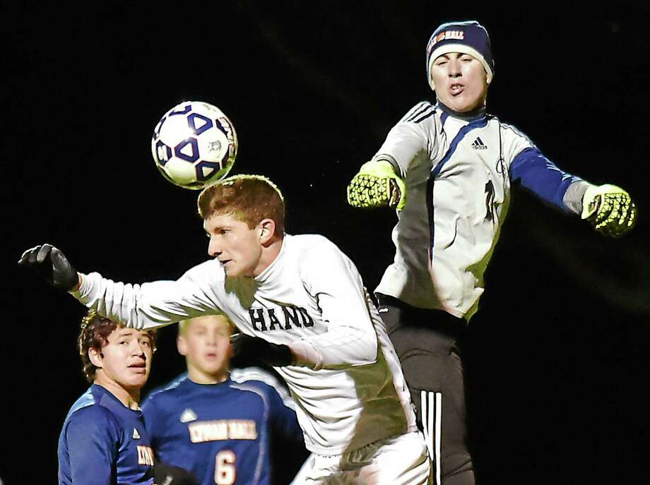 Hand junior Drew Montgomery battles Lyman Hall goalie Brendan O'Connell in a 4-0 win for the Tigers in the Class L quarterfinals this weekend in Madison. Photo: Catherine Avalone -- New Haven Register   / Catherine Avalone/New Haven Register