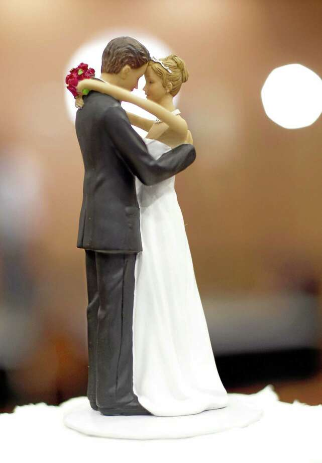 Figurines of a bride and a groom sit atop a wedding cake. Photo: AP Photo/The News & Observer, Robert Willett   / The News & Observer