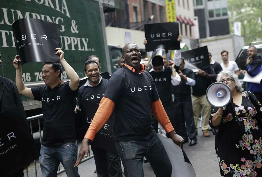 Uber drivers and their supporters protest in front of the offices of the Taxi and Limousine Commission in New York in May. Uber and Lyft are pushing back against a New York City effort to regulate app-based car services. Photo: Seth Wenig — The Associated Press   / AP