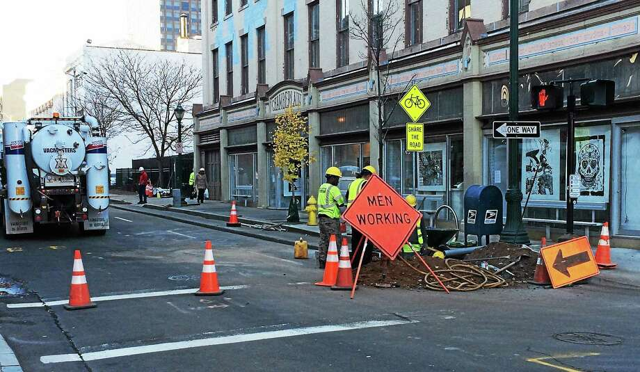 (Wes Duplantier -- New Haven Register) Part of Crown Street remained shut down Monday afternoon as crews worked to repair a gas line hit by construction workers earlier in the day. The resulting leak prompted the brief evacuations of nearby buildings and High School in the Community. Photo: Journal Register Co.