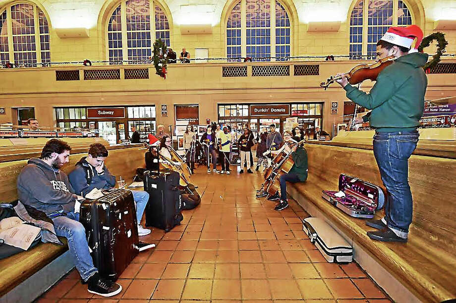 "Noel Mitchell, 15, a student violinist at Music Haven plays ""Dona Nobis Pacem,"" which is Latin for ""Grant Us Peace"" at Union Station in New Haven Thursday during a classical version of a flash mob. ""That was pretty cool and expected,"" said Berk Cindik, 18, of Turkey traveling with his schoolmate Oleg Lyubimov, 17, of Russia, sitting opposite Mitchell. Photo: Catherine Avalone — New Haven Register / Catherine Avalone/New Haven Register"