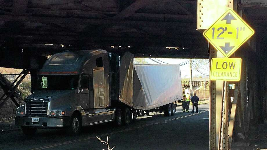 (Wes Duplantier -- New Haven Register) James Street was shut down between State and Lombard streets in New Haven early Monday afternoon after a tractor-trailer crashed into the low-hanging railroad bridge that runs over the road. The truck driver said he didn't see the bright yellow signs warning of the bridge's height. Photo: Journal Register Co.