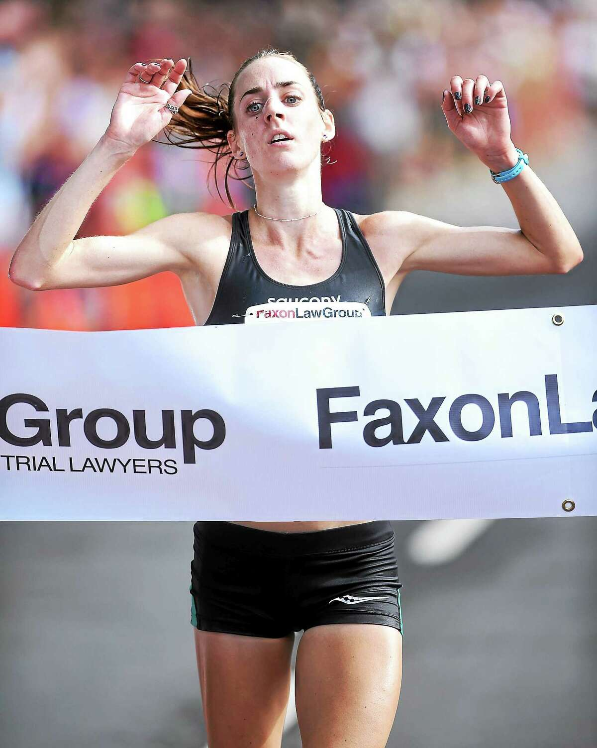(Arnold Gold-New Haven Register) Molly Huddle crosses the finish line of the 37th Annual Faxon Law New Haven Road Race on 9/1/2014. She was the first women's finisher.