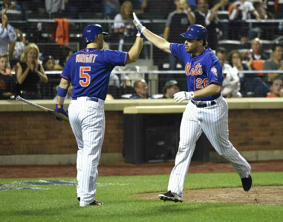 The Mets' David Wright (5) greets Daniel Murphy (28) at home plate after Murphy hit a solo home run off of New York Yankees starting pitcher Masahiro Tanaka in the sixth inning Friday. Photo: Kathy Kmonicek  — The Associated Press   / FR170189 AP