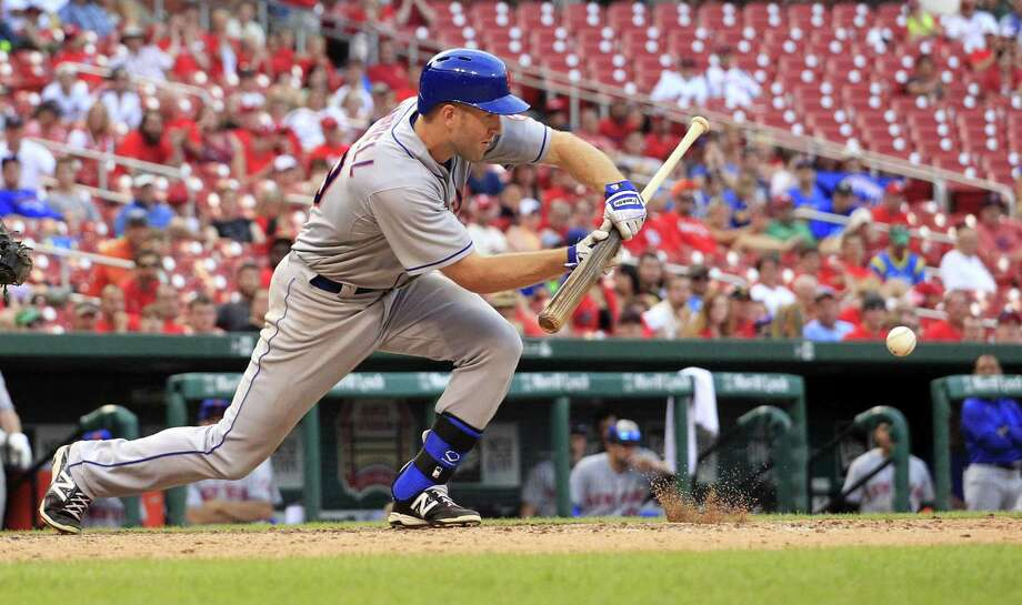 The Mets' Eric Campbell lays down a bunt to score Curtis Granderson during the 18th inning Sunday. Photo: Jeff Roberson — The Associated Press   / AP