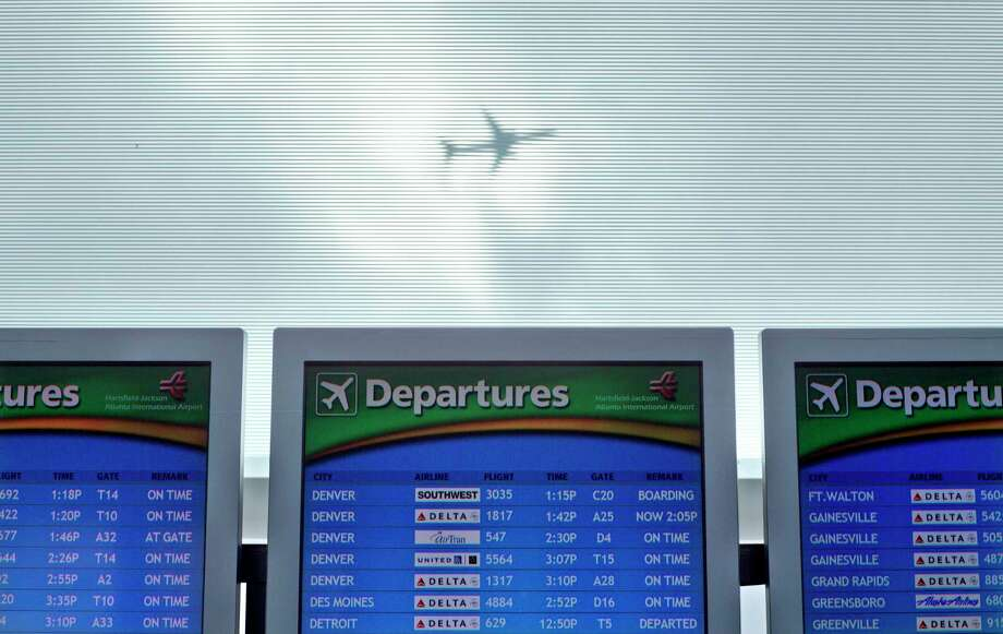 In this Nov. 27, 2013 photo, a plane takes off over a departure board at Hartsfield-Jackson Airport in Atlanta. Caregivers face an assortment of challenges when traveling with a frail relative or friend or with someone with dementia. Packing medications, getting to and from the airport and managing schedules and family activities all can be difficult. Photo: AP Photo/David Goldman, File   / AP