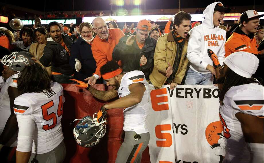 Oklahoma State fans celebrate with the players after their 35-31 victory over Iowa State on Saturday. Photo: Justin Hayworth — The Associated Press   / FR170760 AP