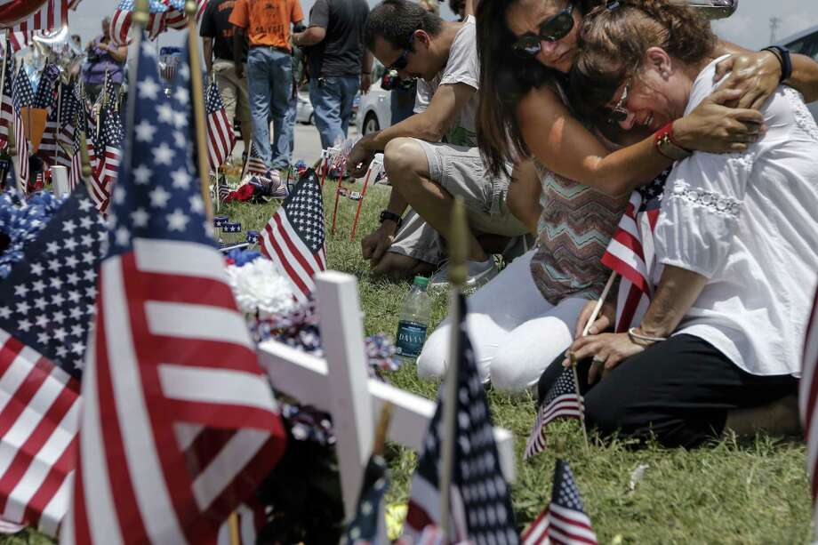 Two women mourn at a makeshift memorial near the Armed Forces Career Center on July 18, 2015, for the victims of the July 16 shootings in Chattanooga, Tenn. The U.S. Navy says a sailor who was shot in the attack on a military facility in Chattanooga has died, raising the death toll to five people. Photo: Doug Strickland/Chattanooga Times Free Press Via AP   / Chattanooga Times Free Press