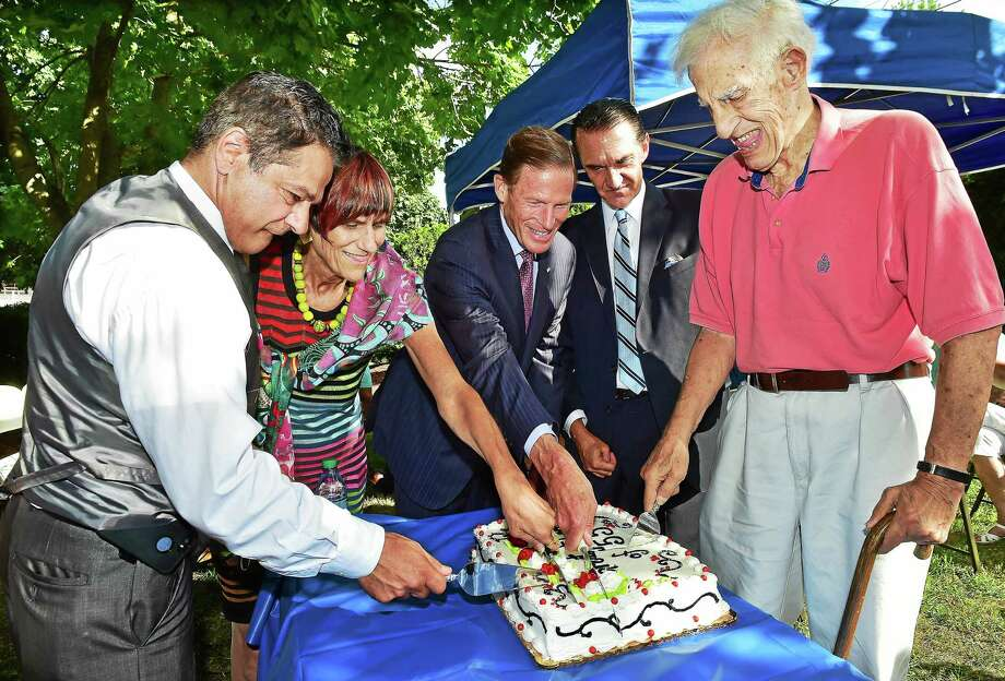 From left, Ansonia Mayor David Cassetti, U.S. Rep. Rosa DeLauro, U.S. Sen. Richard Blumenthal, Greg Stamos and Ted Vartelas cut the cake as Ansonia commemorates the 60th anniversary of the Flood of 1955 Wednesday on the bank of the Naugatuck River at Vartelas Park on Olson Drive in Ansonia. Photo: Catherine Avalone — New Haven Register   / Catherine Avalone/New Haven Register