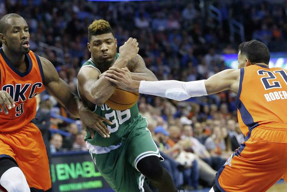 Celtics guard Marcus Smart (36) drives between Thunder forward Serge Ibaka and guard Andre Roberson during the third quarter on Sunday. Photo: Sue Ogrocki — The Associated Press   / AP