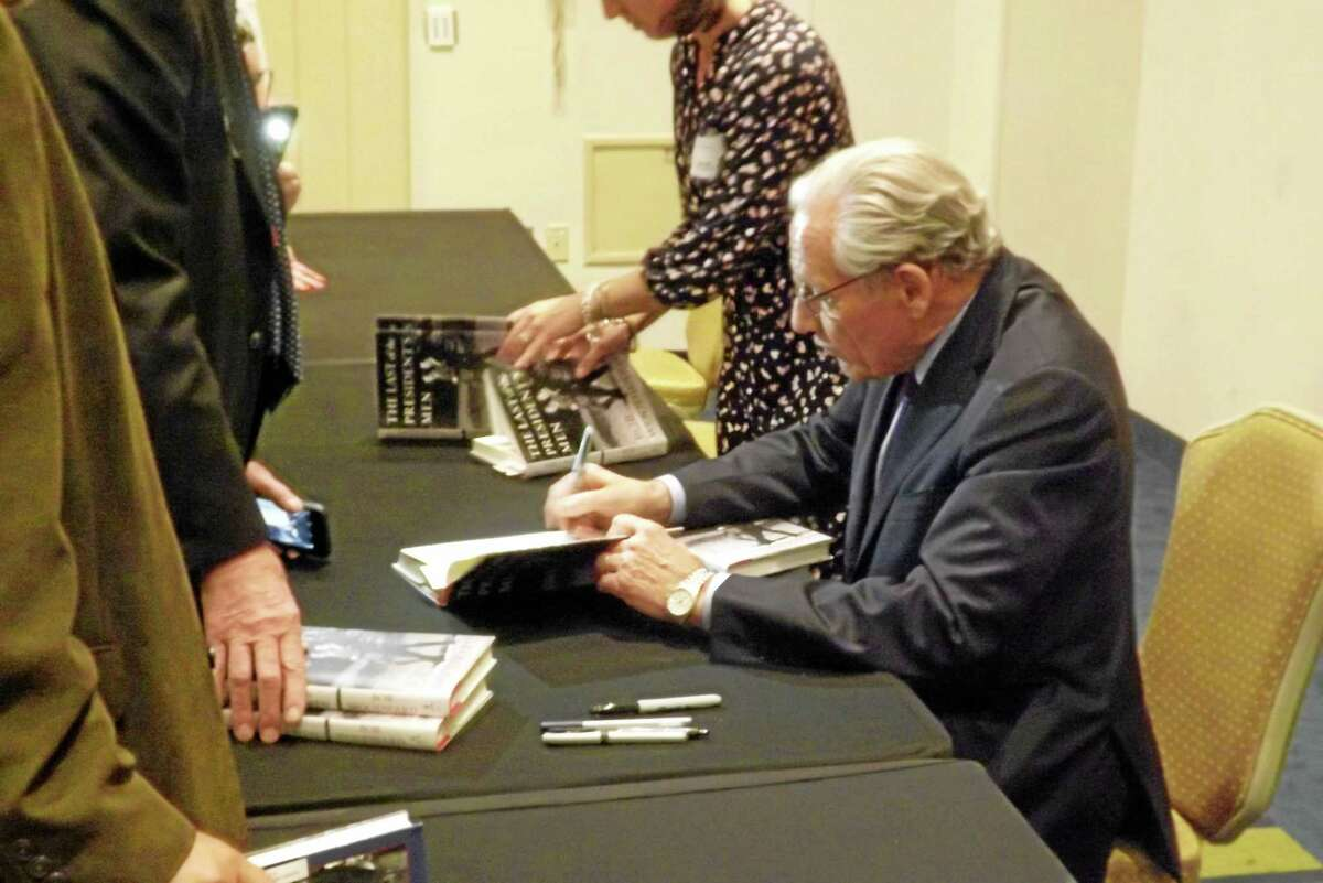 Woodward signs books, more than 100 of which were sold by R.J. Julia Booksellers at the event prior to the luncheon.