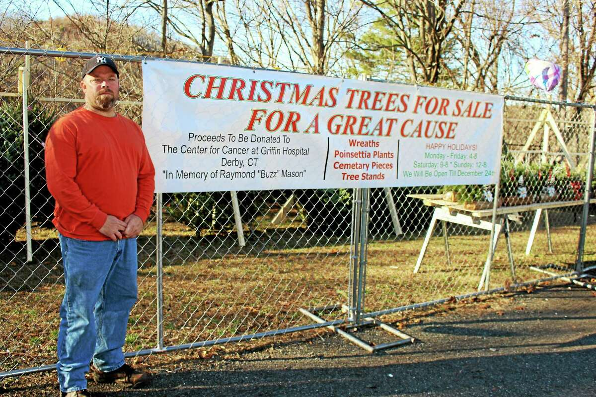 """Harry Danley Jr., a member of Ansonia's Public Works crew, set up a Christmas tree stand to raise funds for cancer and honor his friend, Raymond """"Buzz"""" Mason, who lost his battle with cancer."""