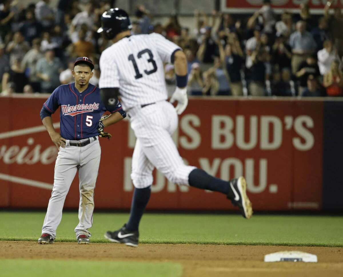 The Twins' Eduardo Escobar (5) watches as New York Yankees' Alex Rodriguez (13) runs the bases after hitting a grand slam that rallied the Yankees from a 4-1 deficit and paved the way for an 8-4 win over Minnesota.