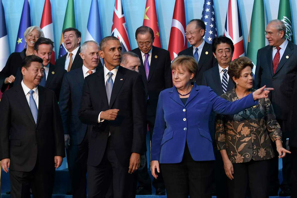 President Barack Obama, center, walks with Germany's Chancellor Angela Merkel, in blue, and other leaders as they try to figure out which way to go following the G20 Summit group photo in Antalya, Turkey on Nov. 15, 2015.