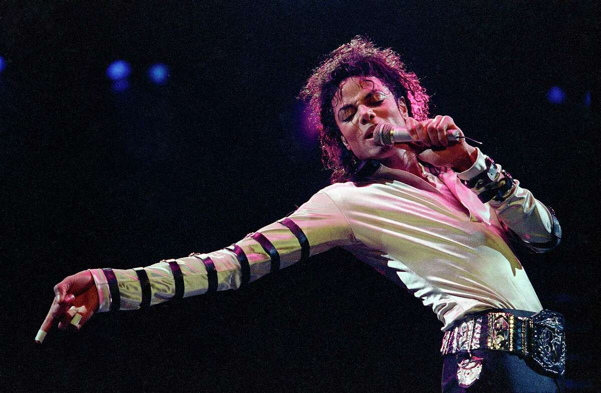 In this Feb. 24, 1988 photo, Michael Jackson leans, points and sings, dances and struts during the opening performance of his 13-city U.S. tour, in Kansas City, Mo.
