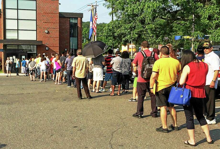 The line was out the door and stretching around the parking lot Tuesday morning at the state Department of Motor Vehicles office on State Street in Hamden. The agency warned of lengthy delays as it reopened Tuesday after a week-long shutdown for a computer upgrade. Photo: Wes Duplantier -- New Haven Register