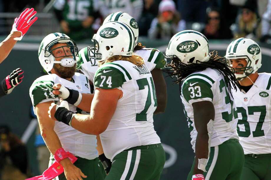New York Jets players celebrate with quarterback Ryan Fitzpatrick, left, after he scored on a touchdown run against Washington on Sunday. Photo: Gary Hershorn — The Associated Press   / FR171392 AP