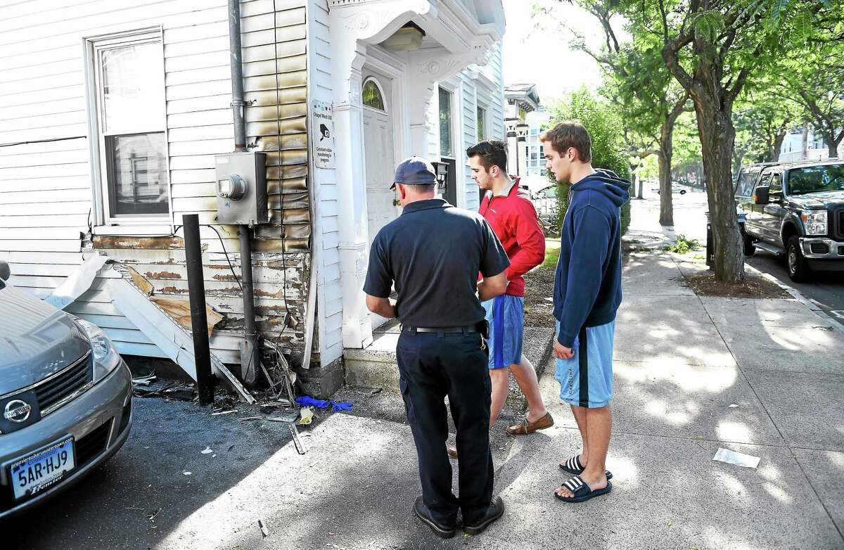 New Haven Fire Investigator Ray Saracco, left, examines fire damage to 397 Crown St. in New Haven with residents of the building Thursday morning.