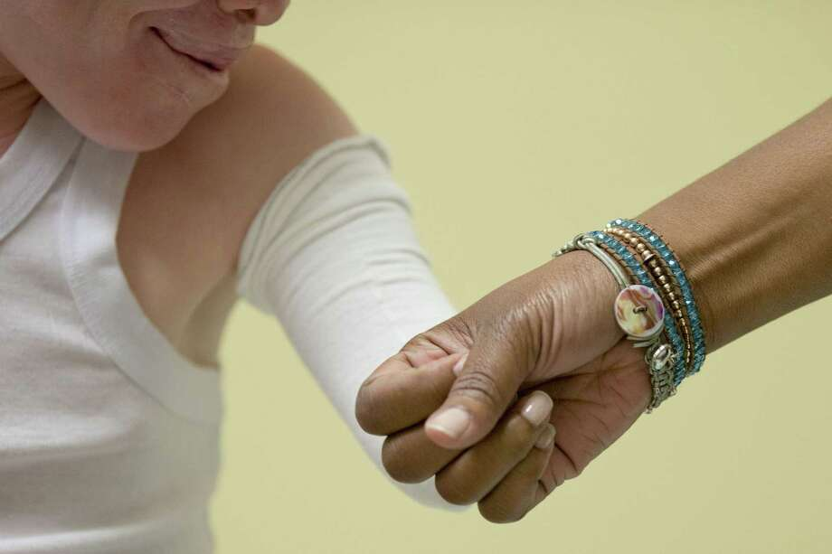 Monica Watson with Global Medical Relief Fund and Emmanuel Rutema, 13, of Tanzania touch during a fitting for prosthetic limbs on July 23, 2015, at Shriners Hospital for Children in Philadelphia. Photo: AP Photo/Matt Rourke   / AP