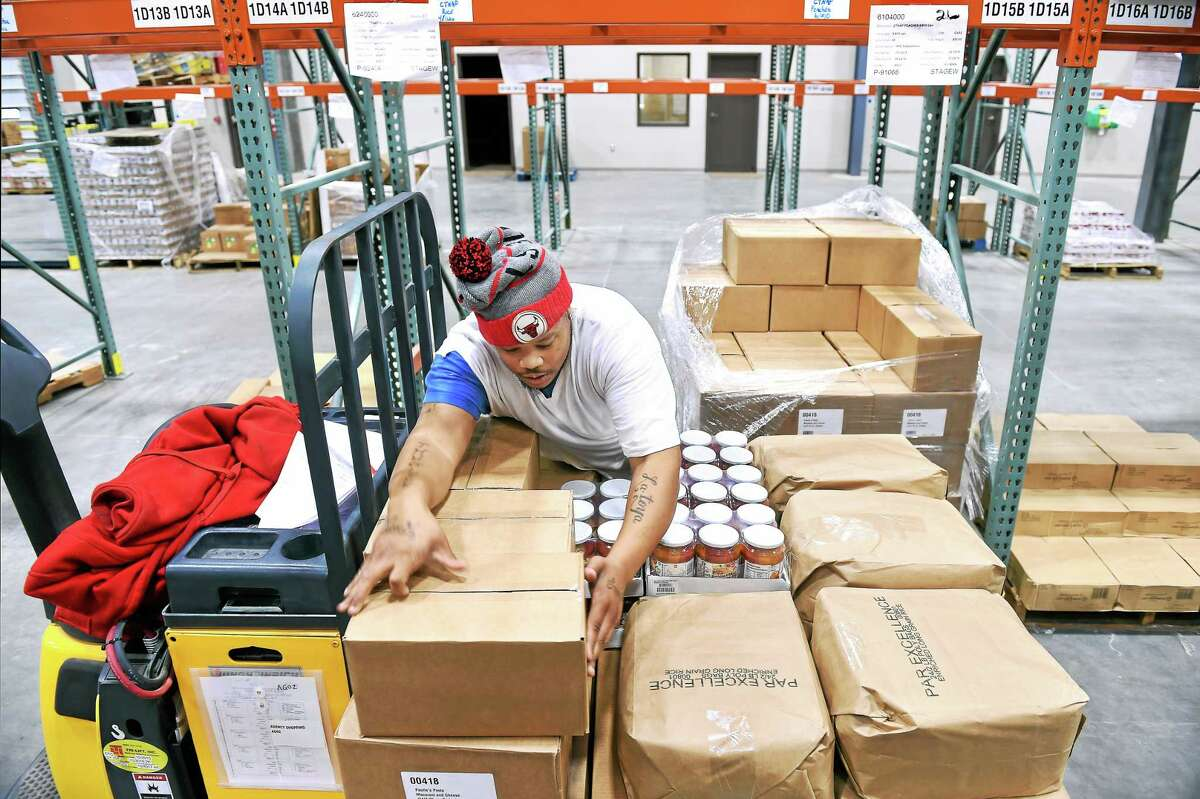 (Arnold Gold-New Haven Register) Usef Norwood puts together an order in the warehouse of the new Connecticut Food Bank facility.