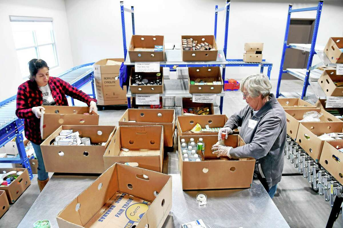 (Arnold Gold-New Haven Register) Erica Savenelli, left, of Madison and Vicki Jones of Hamden sort through food at the new Connecticut Food Bank facility in Wallingford last week.