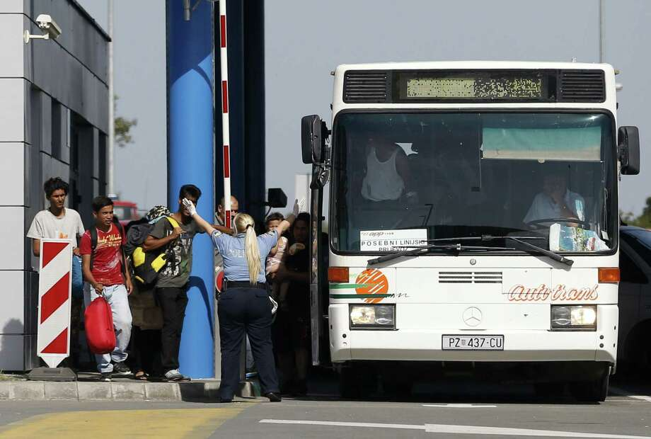 Croatian police officers take control  the bus at the Batina border crossing with  Serbia, that would take migrants to the center for asylum seekers, near Batina, Croatia on Sept. 17, 2015. Thousands of migrants poured into Croatia on Thursday, setting up a new path toward Western Europe after Hungary used tear gas and water cannons to keep them out of its territory. Photo: AP Photo/Darko Vojinovic   / AP