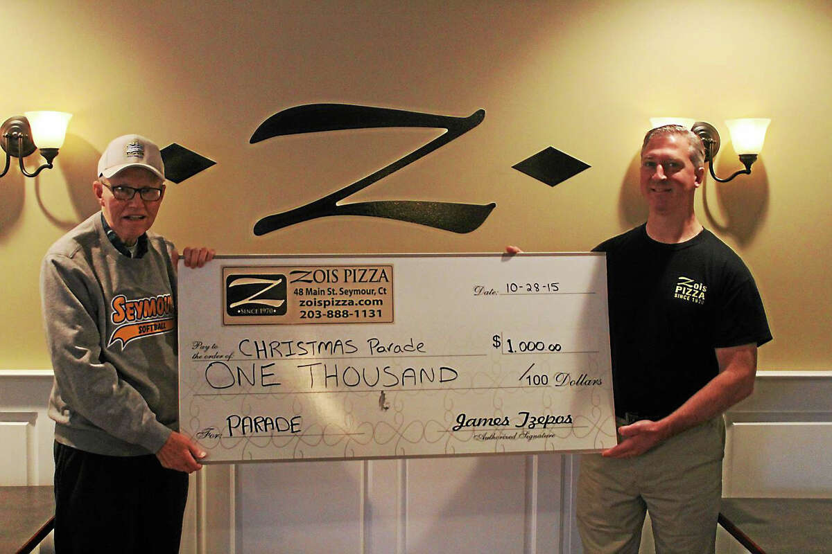 Parade Association President Robert Lang (left) and Jimmy Tzepos of Zois Pizza hold a $1,000 check donated by Tzepos to help out on the annual Christmas parade.
