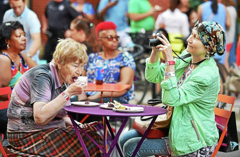 Valentina Nikilina enjoys a slice of blueberry pie, and her daughter, Svetlana Kuzmenko, captures the moment at Pie On9, a fundraiser for CitySeed's food stamp double-value program, held Aug. 7 in New Haven's 9th Square. Both are Moscow residents. Photo: Catherine Avalone — New Haven Register    / Catherine Avalone/New Haven Register