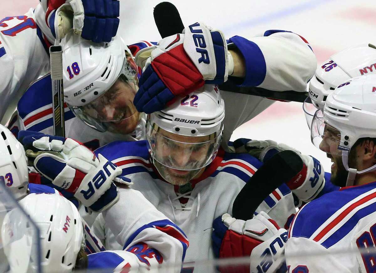 The Rangers' Dan Boyle, center, celebrates his shootout goal with teammates after New York's 2-1 win over the Senators on Saturday in Ottawa.