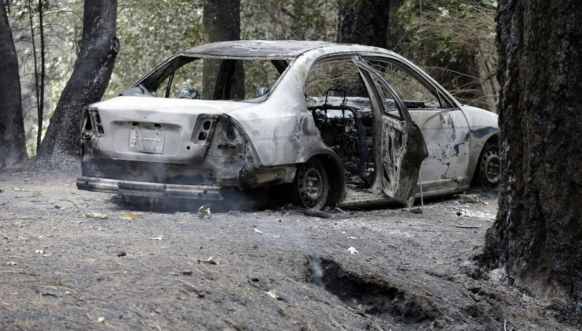 The charred remains of a car belonging to Leonard Neft, who has been missing since a wildfire tore through the area and destroyed his home days earlier, sits in the Anderson Springs area Sept. 16, 2015, near Middletown, Calif.