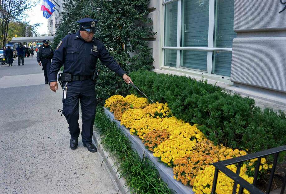 A New York City police officer looks into flower beds at the French consulate in New York, Saturday, Nov. 14, 2015, in the wake of a terrorist attack in Paris Friday. French officials say at least 127 people were killed in shootings and explosions at a theater, restaurant and elsewhere in Paris. Photo: AP Photo/Craig Ruttle    / FR61802 AP